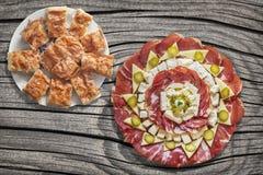 满盘塞尔维亚传统Gibanica弄皱了与食家在老破裂的野餐桌上设置的开胃菜美味盘的乳酪饼 库存图片