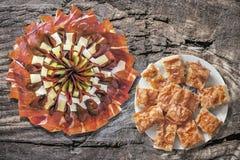满盘塞尔维亚传统Gibanica弄皱了与食家在老破裂的野餐桌上设置的开胃菜美味盘的乳酪饼 图库摄影