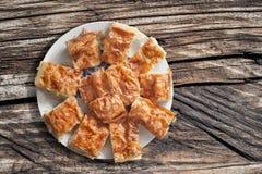 满盘塞尔维亚传统Gibanica弄皱了乳酪在老木被打结的破裂的野餐桌上设置的饼切片 免版税库存图片