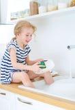 洗盘子的愉快的小女孩 免版税图库摄影