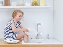 洗盘子的愉快的小女孩 免版税库存照片