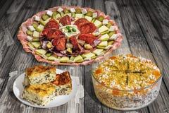满盘开胃菜美味与Gibanica弄皱了在老破裂的木庭院和盘设置的乳酪奥利维尔沙拉饼Tabe 图库摄影