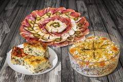 满盘开胃菜美味与Gibanica弄皱了在老破裂的木庭院选项和盘设置的乳酪奥利维尔沙拉饼 免版税库存图片