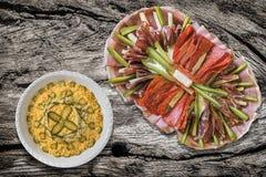 满盘开胃菜美味盘和碗奥利维尔在老土气被风化的被打结的破裂的野餐桌上的沙拉集合 免版税库存图片