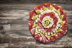 满盘开胃菜美味盘在老破裂的片状木庭院表上设置的Meze 免版税库存照片