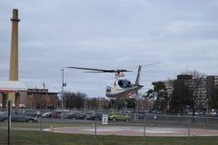 盘旋在与医院军医商标的停机坪的直升机 免版税库存图片