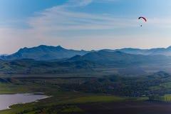 盘旋在多小山风景上的老练的吊滑翔机 免版税库存图片