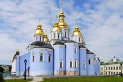 盘旋在天空的蓝色的一只孤独的鸟在教会的金黄圆顶的上 免版税库存图片