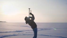 盘旋在高兴音乐家附近射击弹喇叭和把它放的外形的向上在冻结的自然背景上 股票录像