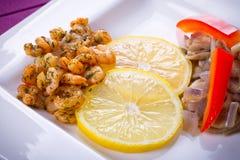 盘用油煎的大虾和柠檬 免版税库存图片