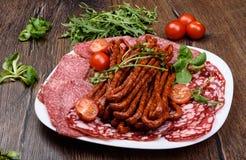 盘用稀薄地切的熏制的香肠 蕃茄和芝麻菜 库存照片