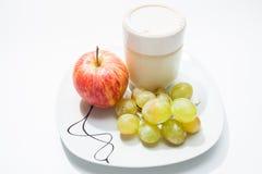 盘用酸奶、苹果和葡萄 免版税图库摄影