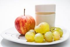 盘用酸奶、苹果和葡萄 免版税库存图片