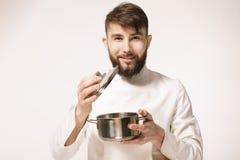 盘的芳香 嗅到食物的主厨站立反对白色背景 嗅到盘的芳香的厨师 库存图片