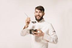 盘的芳香 嗅到食物的主厨站立反对wh 免版税库存图片