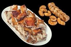 满盘食家唾液与芝麻新月形面包油酥点心辫子和乳酪在黑背景隔绝的劳斯的烤猪肉切片 图库摄影
