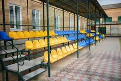 盛大立场的空的蓝色和黄色体育位子在后院的体育场的学校 免版税库存照片