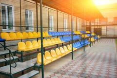 盛大立场的空的蓝色和黄色体育位子在后院的体育场的学校 库存照片