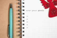 目标、笔记本和绿色笔与木红色天使 库存照片