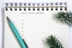 目标、笔记本和绿色笔与针叶树分支 免版税图库摄影
