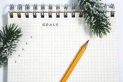 目标、笔记本和黄色铅笔有针叶树的分支 免版税图库摄影