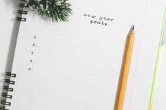 目标、笔记本和黄色铅笔有针叶树的分支 库存照片