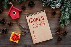 目标名单在2018年 在云杉的分支和杉木锥体附近的笔记本在木背景顶视图 免版税库存照片