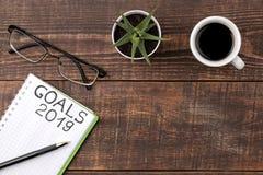 目标在2019年 在笔记本的文本有笔、玻璃和咖啡的在棕色木背景 库存图片