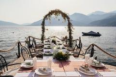 目的地婚礼曲拱和banqouet盖了桌在日落 免版税库存图片