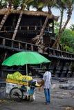 目的地玻璃扩大化的映射旅行 有他的玉米棒子的一个人,卖烤玉米 Canggu,巴厘岛,印度尼西亚2016年10月02日 免版税图库摄影