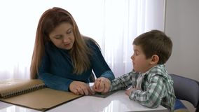 盲人孩子的教育,母亲教儿童男孩在明亮的屋子里写坐在桌上的盲人识字系统 股票视频