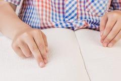 盲人男孩读在盲人识字系统写的一本书 库存图片