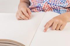盲人男孩读在盲人识字系统写的一本书 免版税库存图片