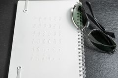 盲人识字系统小点-没有看见的读书 在笔记本后面的盲人识字系统字母表  库存照片