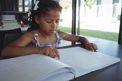 读盲人识字系统的女孩在书桌在图书馆里 免版税库存图片
