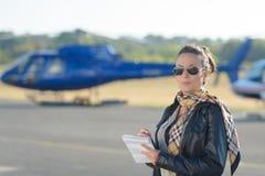 直升机背景的俏丽的试验妇女 免版税库存图片