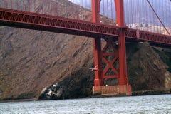 直升机飞行在红色桥梁下 库存照片