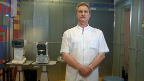 直向前看与在他的面孔的严肃的神色的成熟ophtolmologist 免版税库存图片