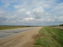 直接柏油路通过乡下在天空下,云彩漂浮 免版税库存照片
