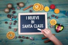 相信克劳斯我圣诞老人 圣诞节和假日背景 装饰品和装饰在一张木桌上 免版税库存图片