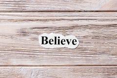 相信在纸的词 概念 词在木背景相信 库存照片