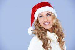 相当一个红色圣诞老人帽子的白肤金发的妇女 免版税库存图片