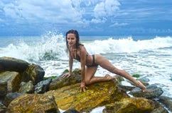 相当一个黑暗的泳装立场的运动的女孩在海滩的大石头在海海洋风暴期间 免版税库存照片