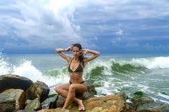 相当一个黑暗的泳装立场的运动的女孩在海滩的大石头在海海洋风暴期间 库存图片