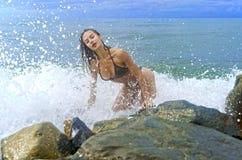 相当一个黑暗的泳装立场的运动的女孩在海滩的大石头在海海洋风暴期间 免版税库存图片