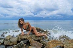 相当一个黑暗的泳装立场的运动的女孩在海滩的大石头在海海洋风暴期间 免版税图库摄影