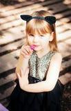 相当一套猫服装的三岁的女孩,有一朵花的在她的手上 库存图片