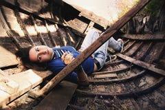 相当一条老木小船的女孩 免版税图库摄影