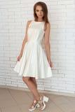 相当一件白色礼服的甜俏丽的女孩在一个砖墙附近的明亮的时尚鞋子在演播室 库存照片