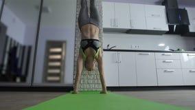 相当与手倒立的运动的妇女锻炼在家 股票录像